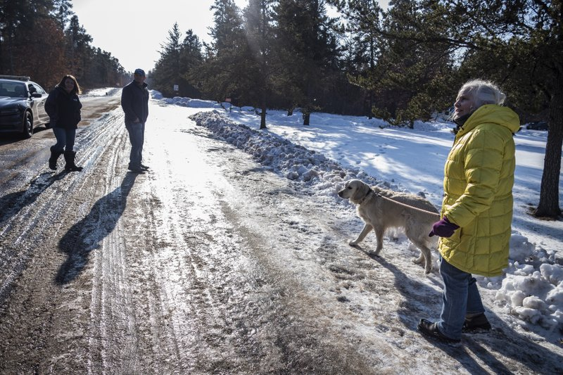 Kristin Kasinskas, left, husband, Peter, and Jeanne Nutter and her dog Henry head back to their homes after speaking with the media Friday, Jan. (Richard Tsong-Taatarii/Star Tribune via AP)