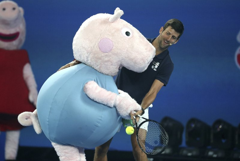 Serbia's Novak Djokovic and Peppa Pig combine to return a shot during Kids Tennis Day ahead of the Australian Open tennis championships in Melbourne, Australia, Saturday, Jan. (AP Photo/Mark Schiefelbein)