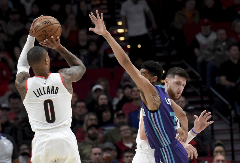 Portland Trail Blazers guard Damian Lillard, left, shoots a basket over Charlotte Hornets guard Jeremy Lamb, center, as center Jusuf Nurkic, right, sets a pick during the first half of an NBA basketball game in Portland, Ore. (AP Photo/Steve Dykes)