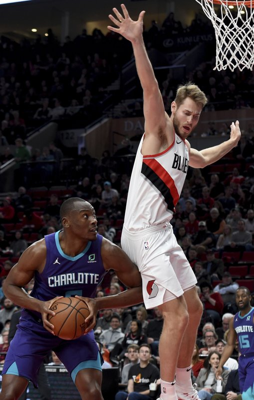 Charlotte Hornets center Bismack Biyombo, left, gets Portland Trail Blazers forward Jake Layman, right, into the air during the first half of an NBA basketball game in Portland, Ore. (AP Photo/Steve Dykes)