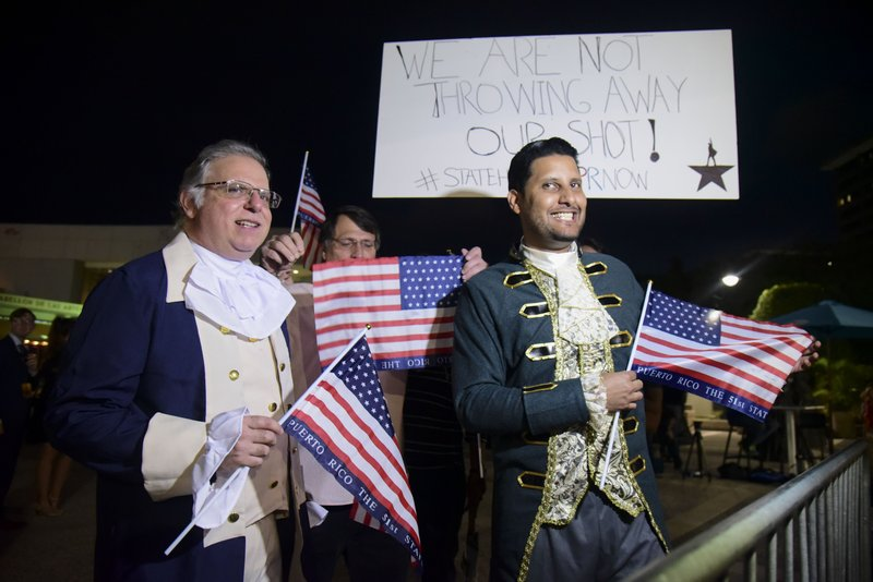Dan Santiago, right, and Miguel Gallo, left, hold a demonstration in favor of statehood at the entrance plaza of the Santurce Fine Arts Center moments before the premiere of the award-winning Broadway musical, Hamilton, starring its creator, New York native of Puerto Rican descent Lin-Manuel Miranda, in San Juan, Puerto Rico, Friday Jan. (AP Photo/Carlos Giusti)
