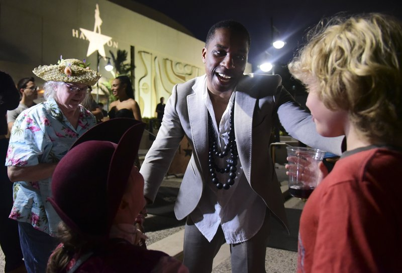Leslie Odom Jr., the actor that plays the role of Aaron Burr greets people at the entrance plaza of the Santurce Fine Arts Center moments before the premiere of the award-winning Broadway musical, Hamilton, starring its creator, New York native of Puerto Rican descent Lin-Manuel Miranda, in San Juan, Puerto Rico, Friday Jan. (AP Photo/Carlos Giusti)