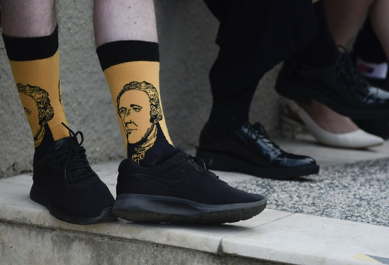 Scotland national Paul Mcque wears Hamilton socks in the entrance plaza of the Santurce Fine Arts Center moments before the premiere of the award-winning Broadway musical, Hamilton, starring its creator, New York native of Puerto Rican descent Lin-Manuel Miranda, in San Juan, Puerto Rico, Friday Jan. (AP Photo/Carlos Giusti)