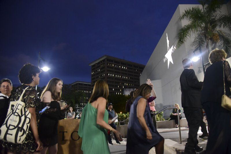 People line up in the entrance plaza of the Santurce Fine Arts Center moments before the premiere of the award-winning Broadway musical, Hamilton, starring its creator, New York native of Puerto Rican descent Lin-Manuel Miranda, in San Juan, Puerto Rico, Friday Jan. (AP Photo/Carlos Giusti)