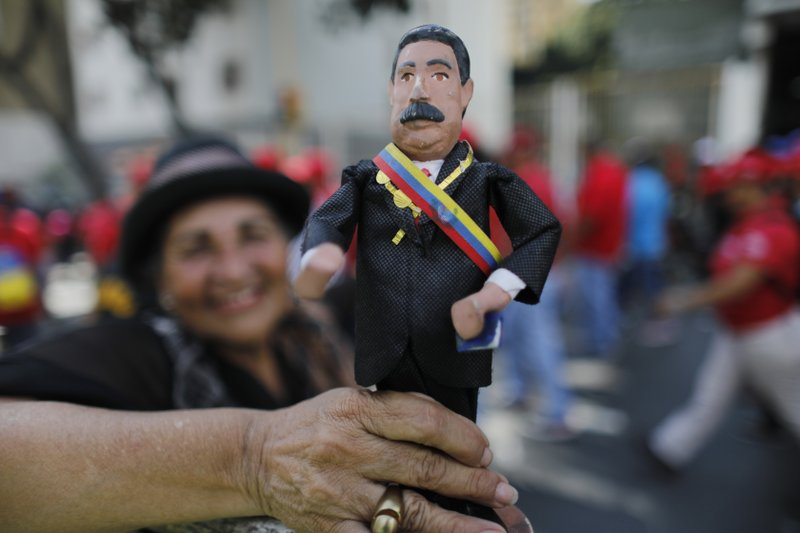 A supporter of Venezuela's President Nicolas Maduro holds a ceramic doll in his likeness outside the Supreme Court where he is being sworn-in for a second term in Caracas, Venezuela, Thursday, Jan. (AP Photo/Ariana Cubillos)