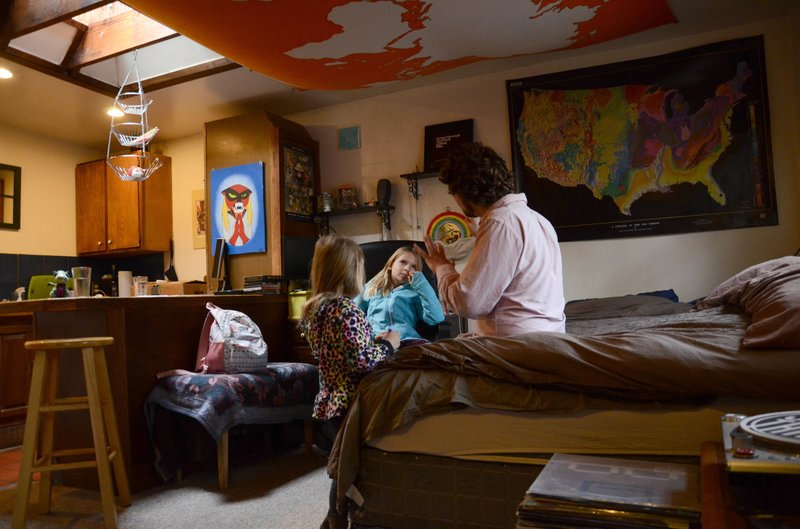 FILE - In this Nov. 28, 2017, file photo, TC Bell sits with his two daughters Dagny, and Emma, before they get dressed for school, at their home in Denver. (AP Photo/Tatiana Flowers, File)