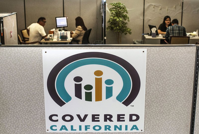 FILE - In this Nov. 1, 2016, file photo, agents help sign people up for insurance through the Covered California exchange at their storefront on Beach Boulevard in Huntington Beach, Calif. (Nick Agro/The Orange County Register/SCNG via AP, File)