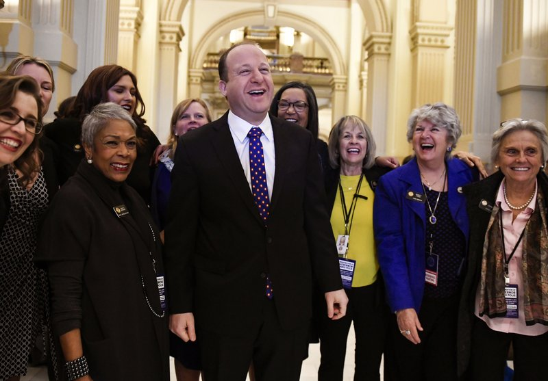 FILE - In this Tuesday, Jan. 8, 2019, file photo, Colorado Governor elect Jared Polis, center, jokes with members of the state house and senate before his inauguration at the Colorado State Capitol in Denver. (AAron Ontiveroz/The Denver Post via AP, File)