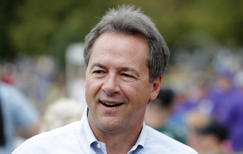 FILE - In this Aug. 16, 2018, file photo, Montana Gov. Steve Bullock walks down the main concourse during a visit to the Iowa State Fair in Des Moines, Iowa. (AP Photo/Charlie Neibergall, File)