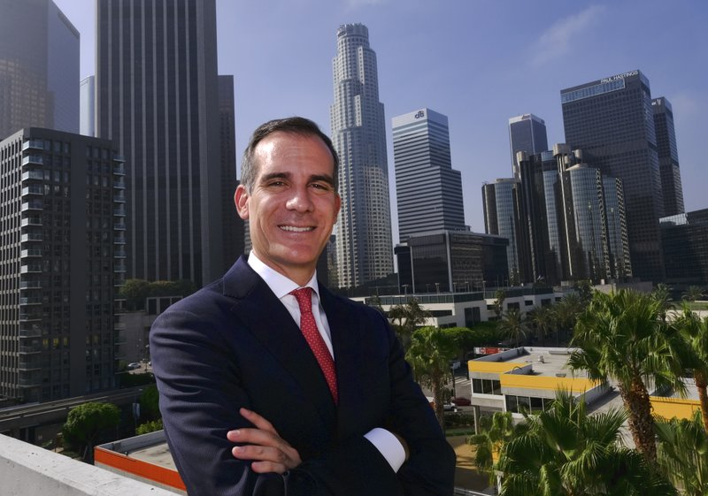 FILE - In this Aug. 23, 2018, file photo Los Angeles Mayor Eric Garcetti poses for a photo in front of a sprawling downtown Los Angeles landscape. (AP Photo/Richard Vogel, File)