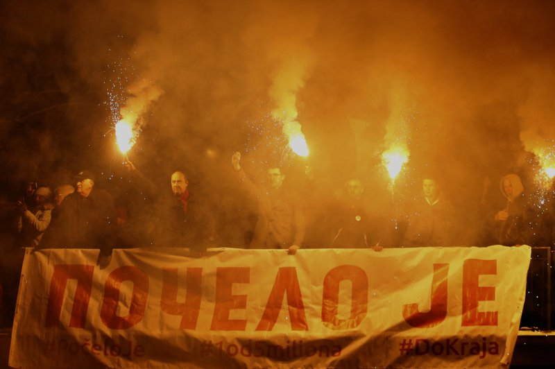 People light torches and hold a banner that reads