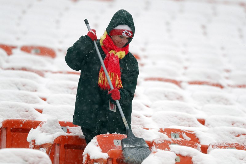 A groundskeeper brushes snow off of seats at Arrowhead Stadium before an NFL divisional football playoff game against the Indianapolis Colts in Kansas City, Mo. (AP Photo/Charlie Neibergall)