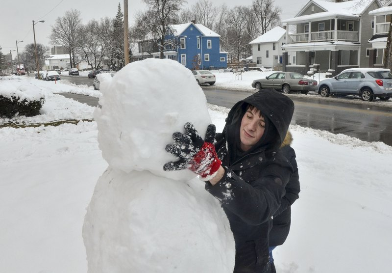 Blake Wise applies the head of the snowman that he and Brianna Atwood built along South 7th Street in Terre Haute, Ind. (Austen Leake/The Tribune-Star via AP)