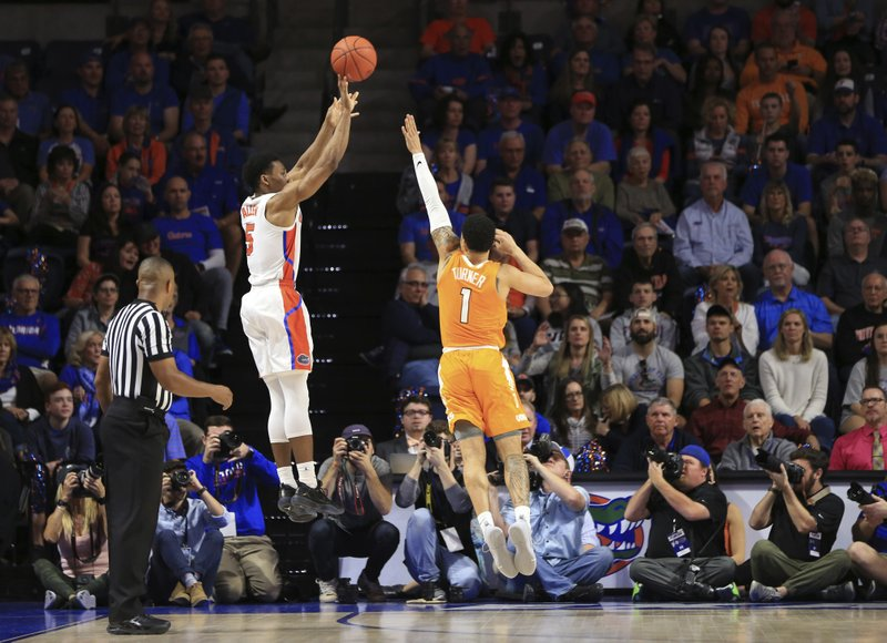 Florida guard KeVaughn Allen (5) makes a 3-point shot over Tennessee guard Lamonte Turner (1) during the first half of an NCAA college basketball game Saturday, Jan. (AP Photo/Matt Stamey)