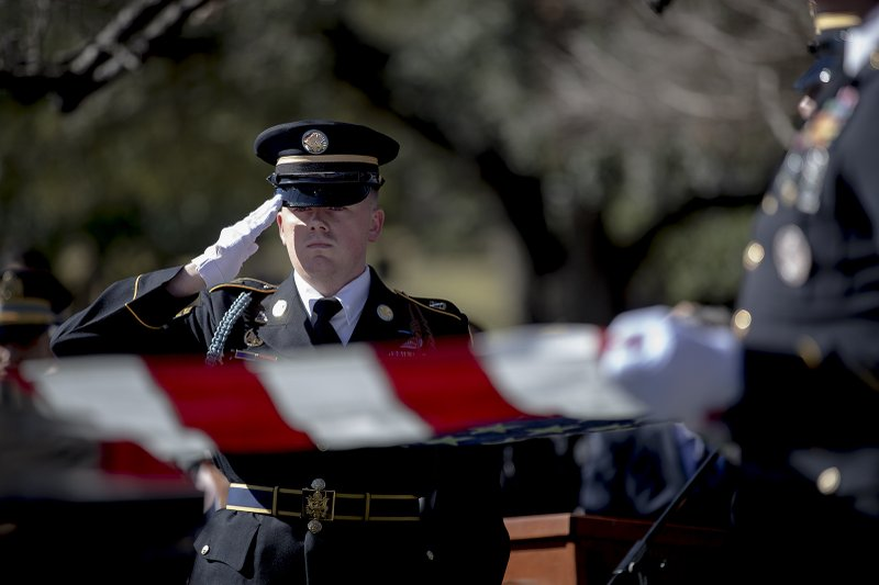 Members of an honor guard readies to fold an American flag that was draped on the casket of WWII veteran Richard Overton during a burial ceremony at the Texas State Cemetery on Saturday, Jan. (Nick Wagner/Austin American-Statesman via AP)
