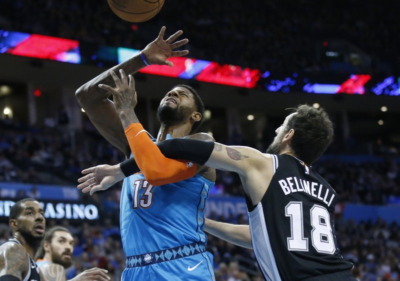 Oklahoma City Thunder forward Paul George (13) loses the ball as he is fouled by San Antonio Spurs guard Marco Belinelli (18) in the first half of an NBA basketball game in Oklahoma City, Saturday, Jan. (AP Photo/Sue Ogrocki)