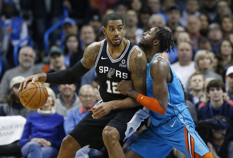 San Antonio Spurs forward LaMarcus Aldridge (12) drives against Oklahoma City Thunder forward Jerami Grant, right, in the first half of an NBA basketball game in Oklahoma City, Saturday, Jan. (AP Photo/Sue Ogrocki)