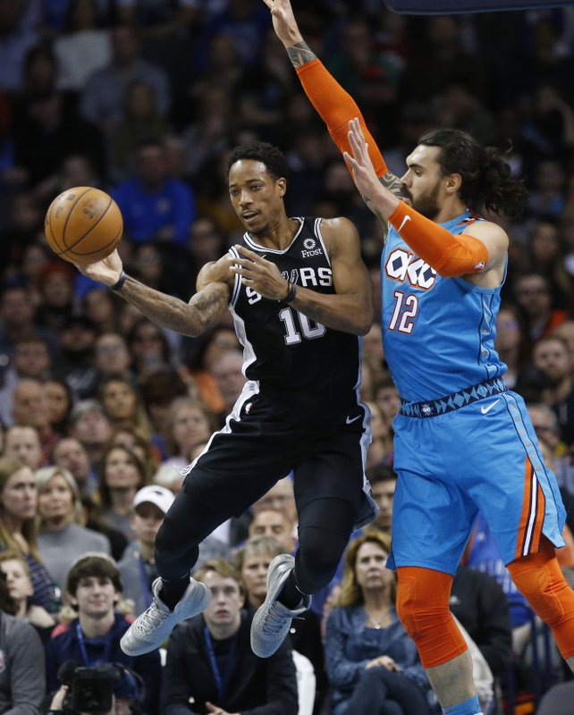 San Antonio Spurs guard DeMar DeRozan (10) passes in front of Oklahoma City Thunder center Steven Adams (12) in the first half of an NBA basketball game in Oklahoma City, Saturday, Jan. (AP Photo/Sue Ogrocki)