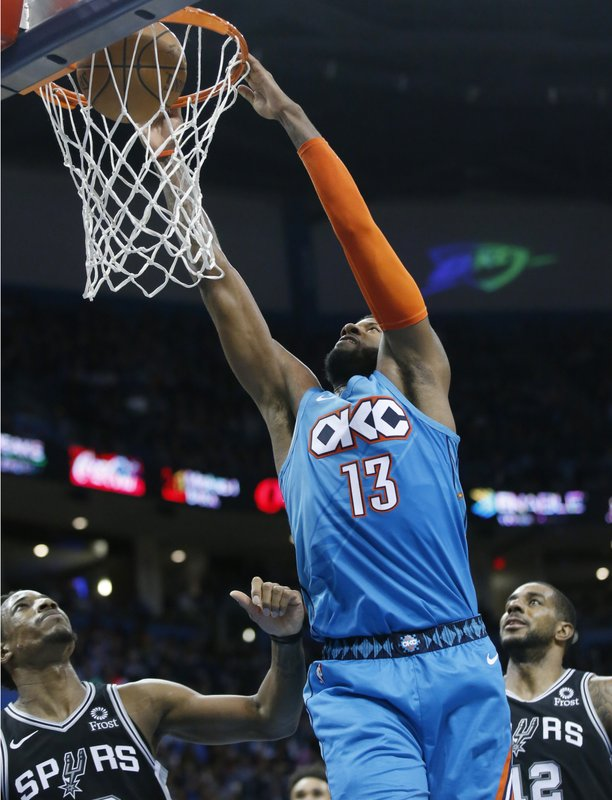 Oklahoma City Thunder forward Paul George (13) dunks between San Antonio Spurs guard DeMar DeRozan, left, and forward Davis Bertans (42) in the first half of an NBA basketball game in Oklahoma City, Saturday, Jan. (AP Photo/Sue Ogrocki)