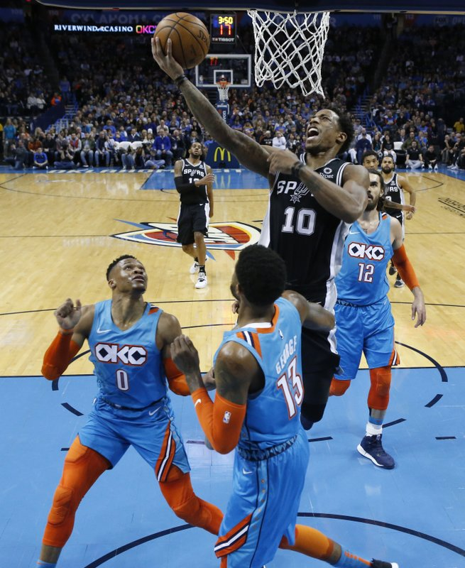 San Antonio Spurs guard DeMar DeRozan (10) goes up for a shot between Oklahoma City Thunder guard Russell Westbrook (0), forward Paul George (13) and center Steven Adams (12) in the first half of an NBA basketball game in Oklahoma City, Saturday, Jan. (AP Photo/Sue Ogrocki)
