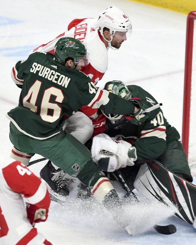 Minnesota Wild's Jared Spurgeon (46) holds off Detroit Red Wings' Luke Glendening, center, as he storms the goal while Wild goalie Devan Dubnyk, right, stops the puck in the first period of an NHL hockey game Saturday, Jan. (AP Photo/Tom Olmscheid)