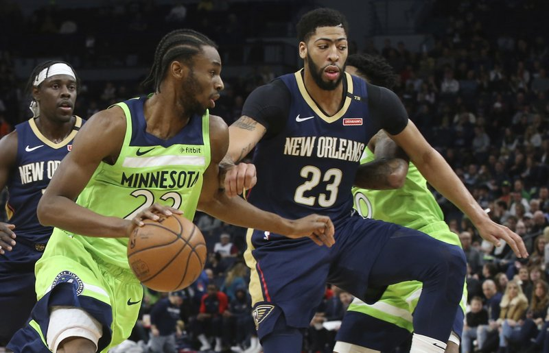 Minnesota Timberwolves' Andrew Wiggins, left, drives past New Orleans Pelicans' Anthony Davis in the first half of an NBA basketball game Saturday, Jan. (AP Photo/Jim Mone)