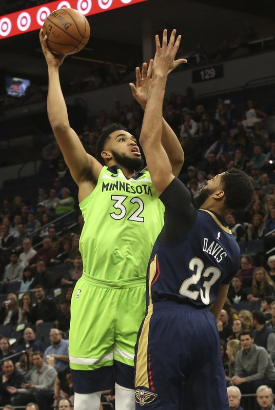 Minnesota Timberwolves' Karl-Anthony Towns, left, shoots over New Orleans Pelicans' Anthony Davis in the first half of an NBA basketball game Saturday, Jan. (AP Photo/Jim Mone)