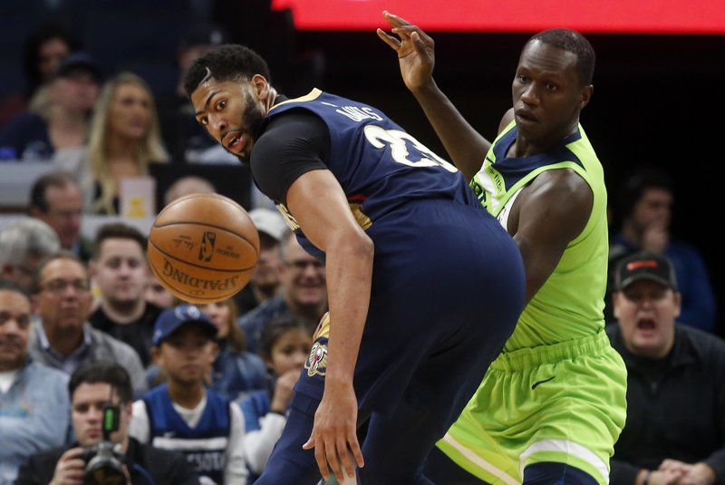 New Orleans Pelicans' Anthony Davis, left, looks at the ball as Minnesota Timberwolves' Gorgui Dieng, of Senegal, defends in the first half of an NBA basketball game Saturday, Jan. (AP Photo/Jim Mone)