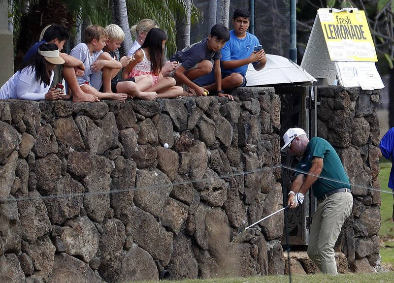 Children watch along the wall as Stewart Cink hits from a backyard along the first fairway during the third round of the Sony Open golf tournament Saturday, Jan. (AP Photo/Matt York)