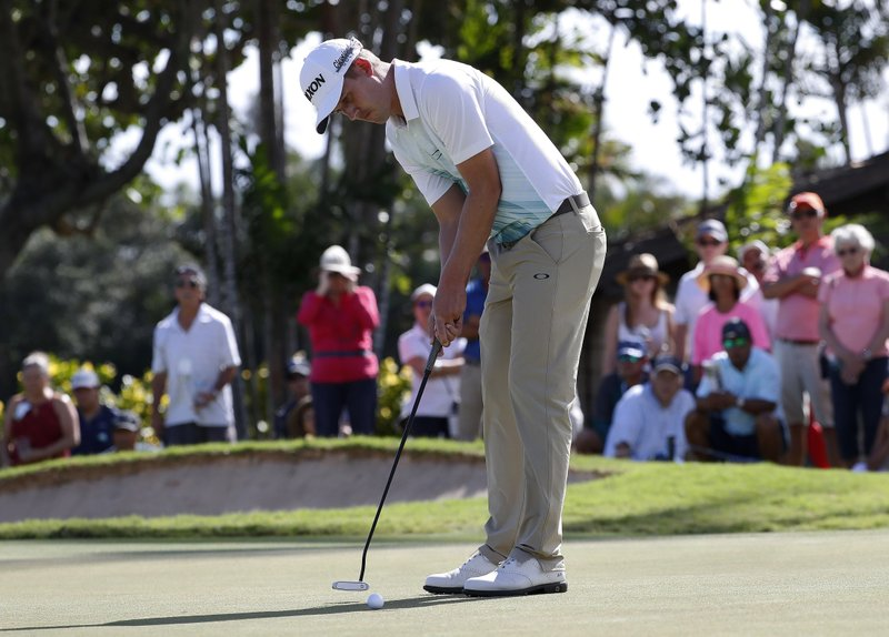 Andrew Putman putts on the third green during the third round of the Sony Open golf tournament Saturday, Jan. (AP Photo/Matt York)