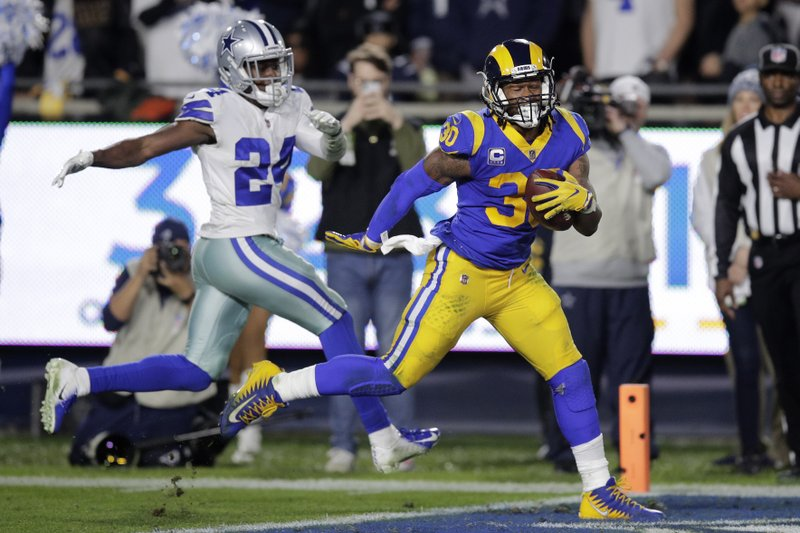Los Angeles Rams running back Todd Gurley scores past Dallas Cowboys cornerback Chidobe Awuzie during the first half in an NFL divisional football playoff game Saturday, Jan. (AP Photo/Jae C. Hong)