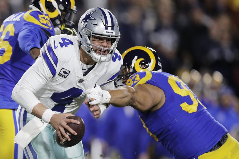 Dallas Cowboys quarterback Dak Prescott breaks away from Los Angeles Rams nose tackle Ndamukong Suh during the first half in an NFL divisional football playoff game Saturday, Jan. (AP Photo/Jae C. Hong)
