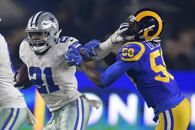 Dallas Cowboys running back Ezekiel Elliott pushes off Los Angeles Rams inside linebacker Cory Littleton during the first half in an NFL divisional football playoff game Saturday, Jan. (AP Photo/Mark J. Terrill)