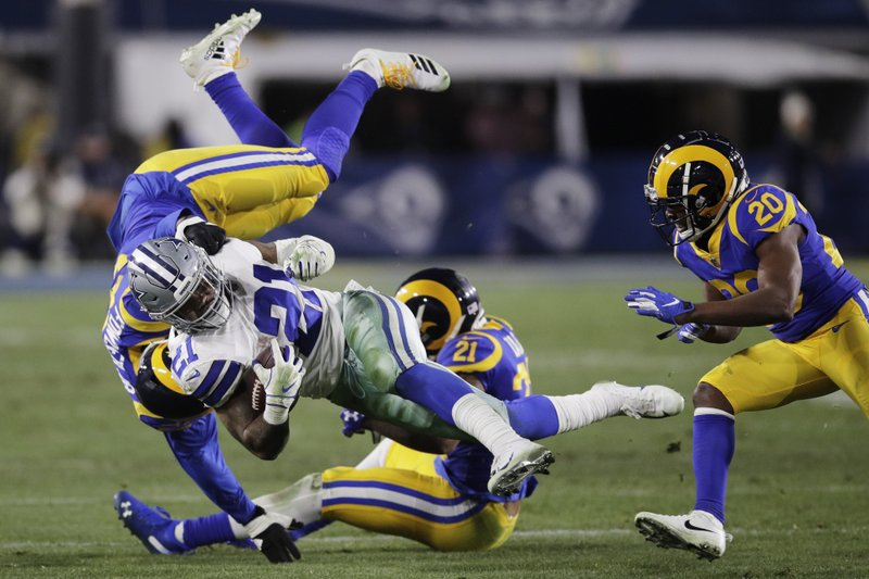 Dallas Cowboys running back Ezekiel Elliott is tackled by Los Angeles Rams linebacker Dante Fowler, top, and cornerback Aqib Talib during the second half in an NFL divisional football playoff game Saturday, Jan. (AP Photo/Jae C. Hong)