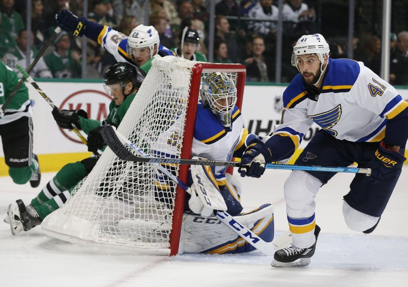 Dallas Stars right wing Erik Condra (27) is pushed into the back of the net by St. Louis Blues defenseman Vince Dunn (29) as Blues goaltender Jordan Binnington (50) and defenseman Robert Bortuzzo (41) defend during the first period of an NHL hockey game in Dallas, Saturday, Jan. (AP Photo/Michael Ainsworth)