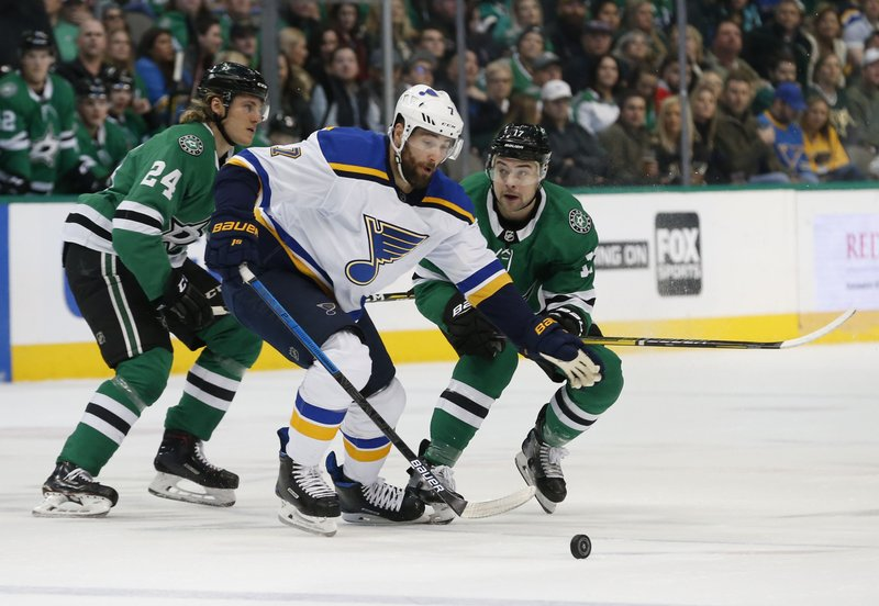 St. Louis Blues left wing Pat Maroon (7) tries to get the puck past Dallas Stars left wing Roope Hintz (24) and center Devin Shore (17) during the first period of an NHL hockey game in Dallas, Saturday, Jan. (AP Photo/Michael Ainsworth)