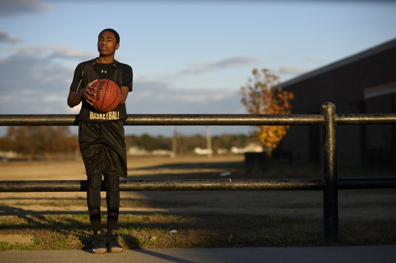 In this Dec. 5, 2018 photo, eighth-grader Ashir Muhammad poses in Fayetteville, N.C. Muhammad is one of the captains for Sampson Middle School boys' basketball team. (Melissa Sue Gerrits/The Fayetteville Observer via AP)