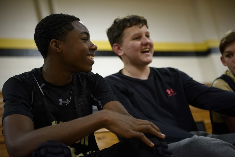 In this Dec. 5, 2018 photo, Ashir Muhammad, left, laughs with teammates while waiting for practice to start at Sampson Middle School in Fayetteville, N. (Melissa Sue Gerrits/The Fayetteville Observer via AP)