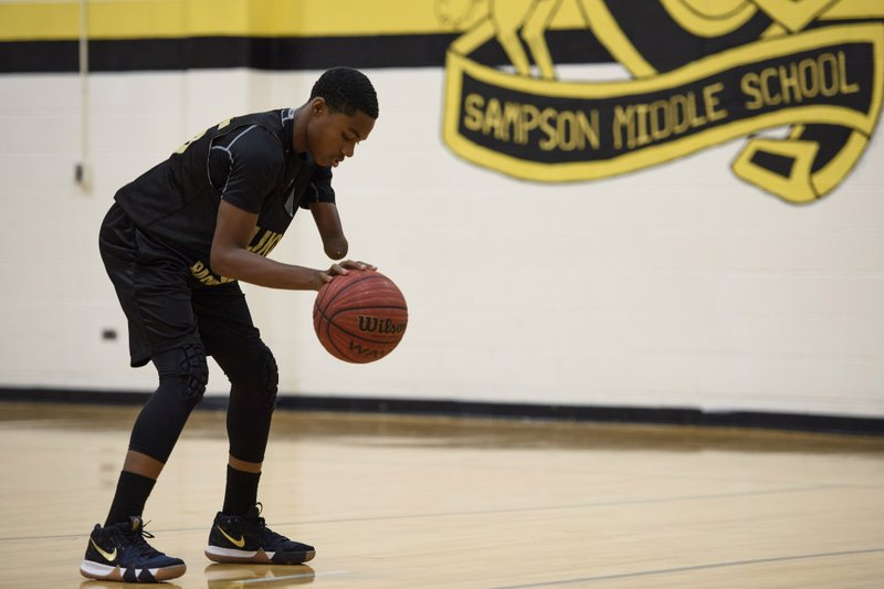 In this Dec. 5, 2018 photo, Ashir Muhammad works on his free throw during team practice at Sampson Middle School in Fayetteville, N. (Melissa Sue Gerrits/The Fayetteville Observer via AP)