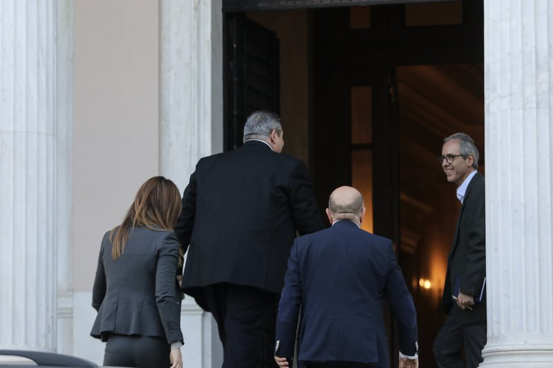Greek Defense Minister Panos Kammenos, second left, arrives for a meeting with Greece's Prime Minister Alexis Tsipras, in Athens, Sunday, Jan. (AP Photo/Yorgos Karahalis)