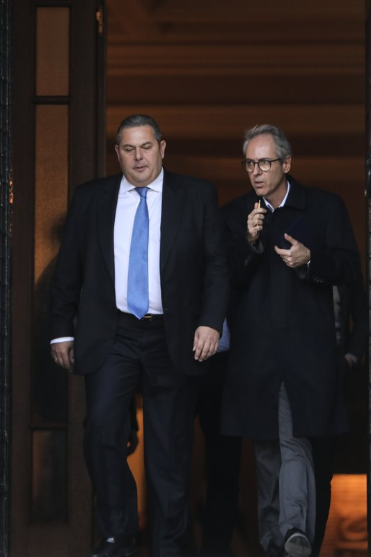 Greek Defense Minister Panos Kammenos, left, leaves Maximos mansion following a meeting with Greece's Prime Minister Alexis Tsipras, in Athens, Sunday, Jan. (AP Photo/Yorgos Karahalis)