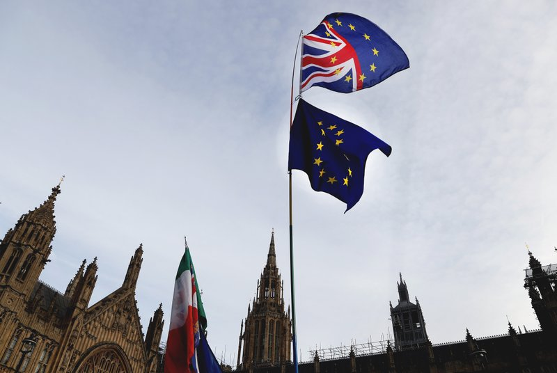 A Pro-European demonstrator raises flags to protest outside parliament in London, Friday, Jan. 11, 2019. (AP Photo/Frank Augstein)