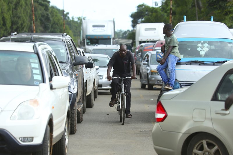 A cyclist makes his way through a fuel queue in the capital Harare, Friday, Jan. 11, 2019. Zimbabwe's president has more than doubled the price of gasoline, hoping the increase will end severe shortages that are fueling public anger. (AP Photo/Tsvangirayi Mukwazhi)