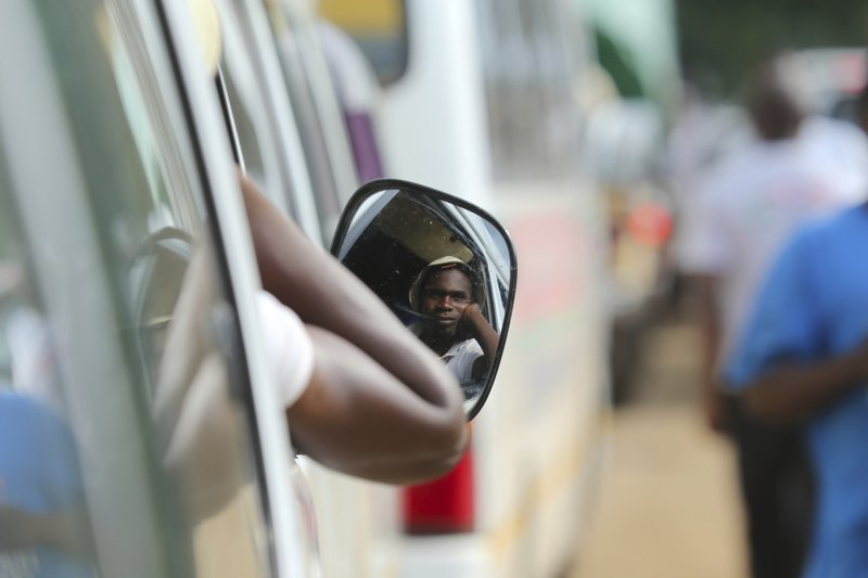 A motorist waits in fuel queue in the capital Harare, Friday, Jan. 11, 2019. Zimbabwe's president has more than doubled the price of gasoline, hoping the increase will end severe shortages that are fueling public anger. (AP Photo/Tsvangirayi Mukwazhi)