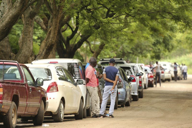 Motorists wait in a fuel queue in the capital Harare, Saturday, Jan. 12, 2019. Zimbabwe's president has more than doubled the price of gasoline, hoping the increase will end severe shortages that are fueling public anger. (AP Photo/Tsvangirayi Mukwazhi)