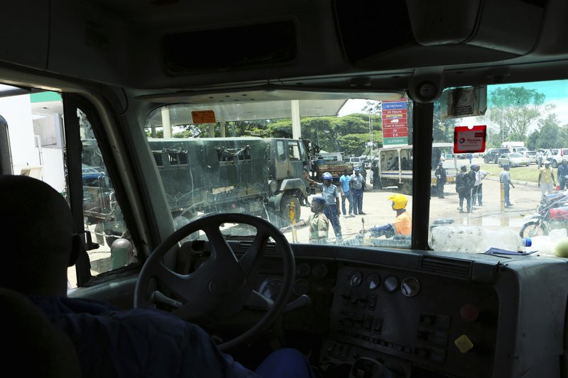 A truck driver waits in a fuel queue controlled by police and the army in the capital Harare, Saturday, Jan. (AP Photo/Tsvangirayi Mukwazhi)
