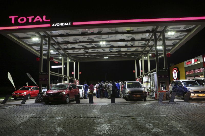 Motorists gather to express their anger after fuel ran out at a gas station in the capital Harare, Tuesday, Jan. (AP Photo/Tsvangirayi Mukwazhi)