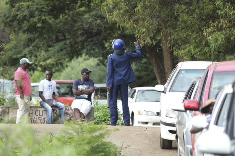 A police officer controls motorists in a fuel queue in the capital Harare, Friday, Jan. 11, 2019. Zimbabwe's president has more than doubled the price of gasoline, hoping the increase will end severe shortages that are fueling public anger. (AP Photo/Tsvangirayi Mukwazhi)