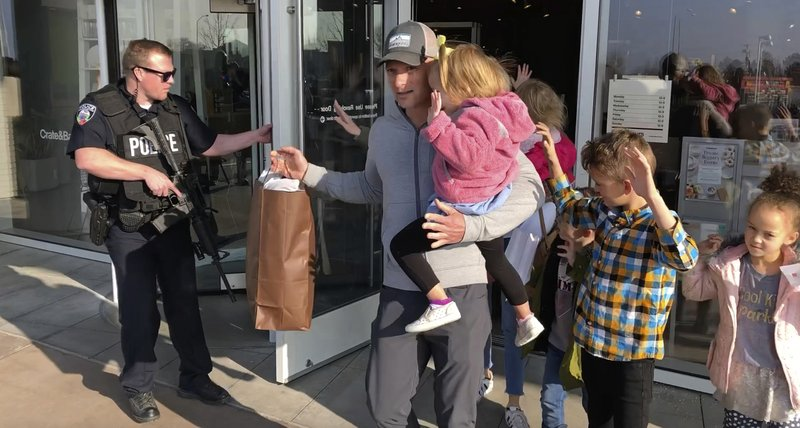 Shoppers with their hands raised are evacuated from Fashion Place Mall in Murray, Utah, after a shooting on Sunday, Jan. (AP Photo/Rick Bowmer)