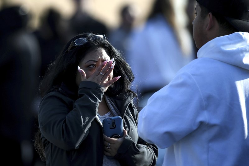 Evelyn Salazar Atwood wipes tears from her eyes after reuniting with her son, Chris Salazar, who works at Fashion Place Mall, after a shooting at the mall in Murray, Utah on Sunday, Jan. (Spenser Heaps/The Deseret News via AP)